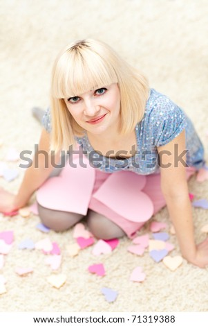 Beautiful young adult sitting on the floor and a lot of paper hearts are around her