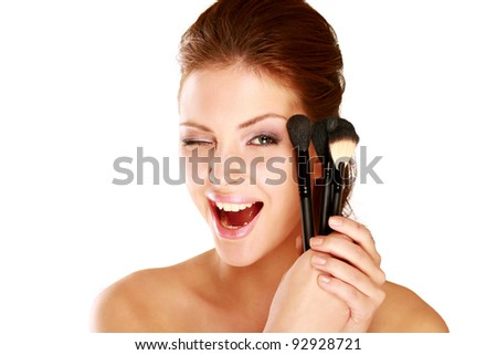 Beautiful young adult woman applying cosmetic paint brush, isolated on white background