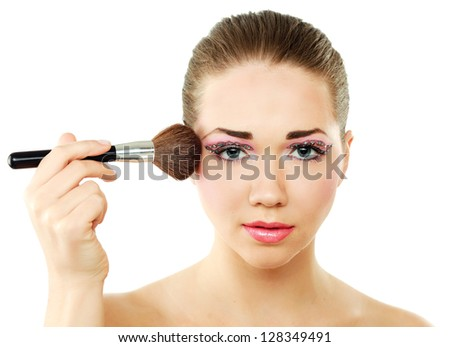 Beautiful young adult woman holds the make-up brushes near attractive face.