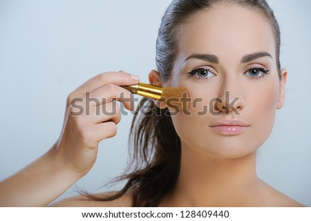 Beautiful young adult woman with healthy skin applying cosmetic on your face