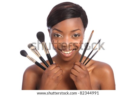 Beautiful young African American beautician woman holding set of six make up brushes. Brush types are powder blusher foundation or base, eye lash separator, brow eye shadow and eye liner brush.