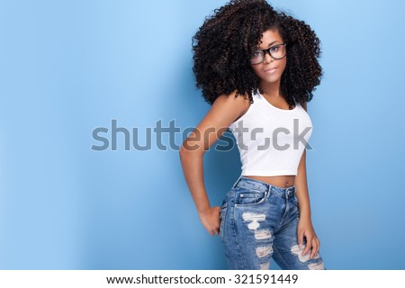 Beautiful young african american girl posing in studio, looking at camera. #321591449