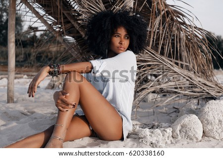 beautiful young african american girl sitting on sand at the beach #620338160