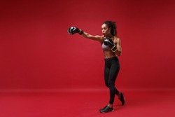 Beautiful young african american sports fitness boxer woman in sportswear working out isolated on red background. Sport exercise healthy lifestyle concept. Doing boxing exercises in boxing gloves