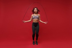 Beautiful young african american sports fitness woman in sportswear posing working out isolated on red background studio portrait. Sport exercises healthy lifestyle concept. Jumping on skipping rope