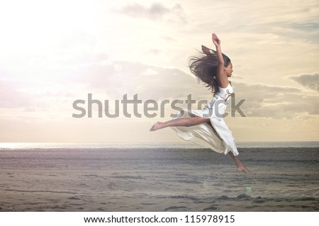 Beautiful young African American woman jumping at the beach