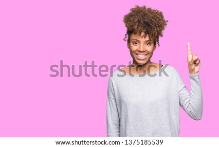 Beautiful young african american woman over isolated background showing and pointing up with finger number one while smiling confident and happy.