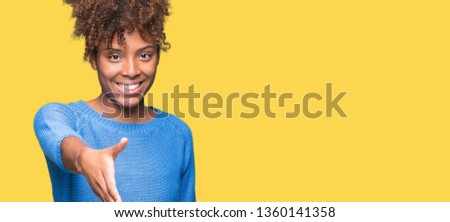 Beautiful young african american woman over isolated background smiling friendly offering handshake as greeting and welcoming. Successful business.
