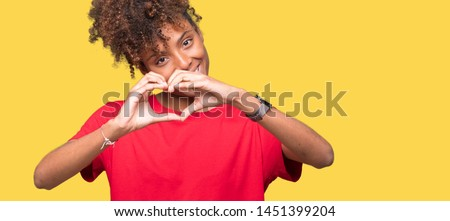 Beautiful young african american woman over isolated background smiling in love showing heart symbol and shape with hands. Romantic concept.