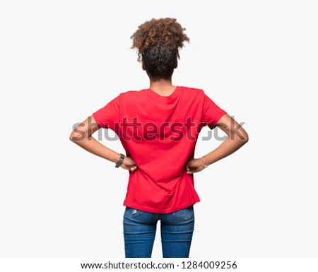 Beautiful young african american woman over isolated background standing backwards looking away with arms on body