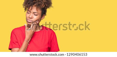 Beautiful young african american woman over isolated background touching mouth with hand with painful expression because of toothache or dental illness on teeth. Dentist concept.