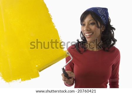 Beautiful Young African American woman painting the wall yellow
