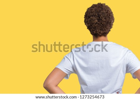 Beautiful young african american woman wearing glasses over isolated background standing backwards looking away with arms on body