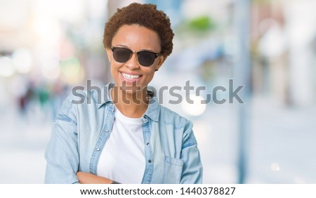 Beautiful young african american woman wearing sunglasses over isolated background happy face smiling with crossed arms looking at the camera. Positive person. #1440378827