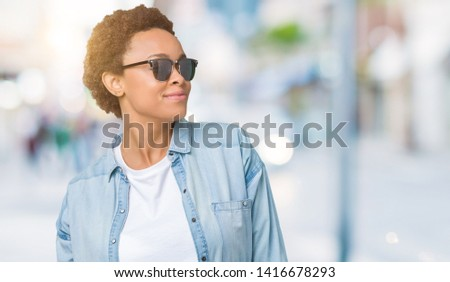 Beautiful young african american woman wearing sunglasses over isolated background looking away to side with smile on face, natural expression. Laughing confident. #1416678293