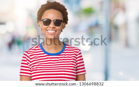 Beautiful young african american woman wearing sunglasses over isolated background with a happy and cool smile on face. Lucky person. #1306698832
