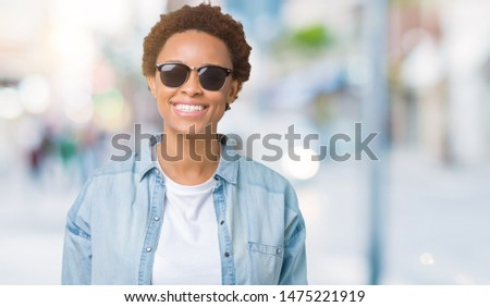Beautiful young african american woman wearing sunglasses over isolated background with a happy and cool smile on face. Lucky person. #1475221919