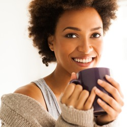 Beautiful young African woman enjoying a cup of coffee.