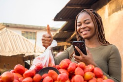 beautiful young african woman in a local african market using her smartphone giving thumbs up