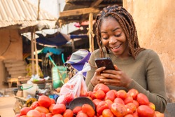 beautiful young african woman in a local african market viewing content on her phone looking surprised