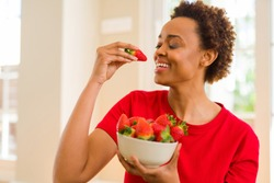 Beautiful young african woman with afro hair eating fresh strawberries