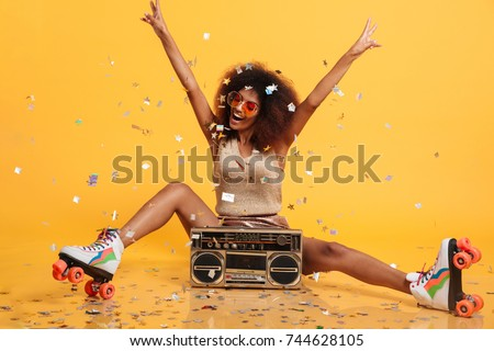 Beautiful young african woman with afro hairstyle throwing confetti, showing peace gesture while sitting in roller skates with boombox, isolated on yellow background