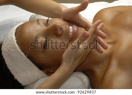 Beautiful young Afro american woman getting a face treatment at beauty salon. Beautiful young black woman getting a face treatment at beauty salon.