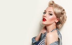 Beautiful young american girl in retro style, pinup. Blond, hairstyle - light curls. Retro make-up - red lips, black arrows. Clothing - jeans jacket and gold jewelry.