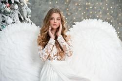 Beautiful young angel woman with big white wings near Christmas tree. Angel. Beautyful girl angel. Christmas.