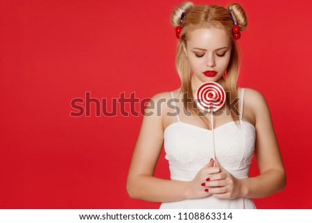 Beautiful young anime girl holding a red white lollipop and smiling. A blonde woman with a hairdo bunch, infantilism and non-seriousness.