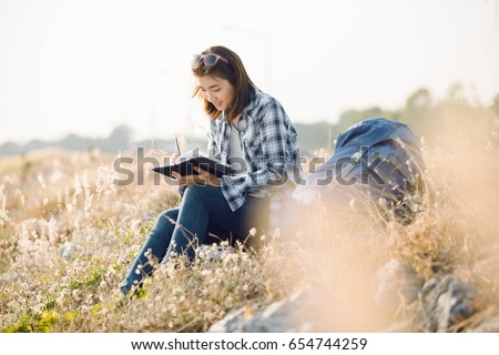 Beautiful young Asia woman writing on a journal about her hiking trip,flare light