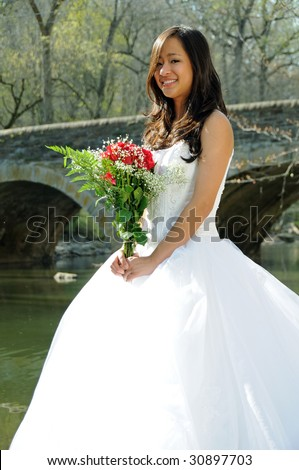 Beautiful young Asian bride by river