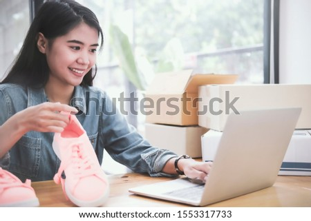 Beautiful young asian business owner working with computer and tablet standing in workshop.Responding on business e-mail,writing the order of product customer orders.