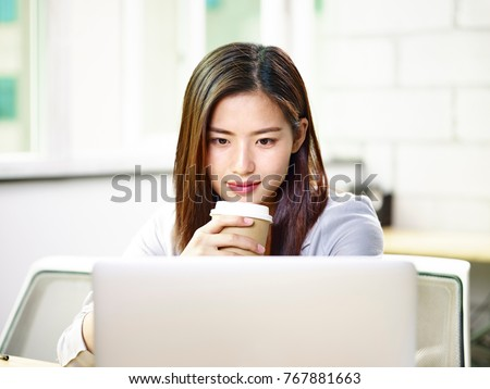 beautiful young asian business woman working in office holding a cup of coffee looking at laptop computer.