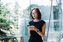 Beautiful young Asian businesswoman in formal black dress and eyeglasses and wristwatch standing surfing mobile at hall of commercial building on background of transparent glass wall