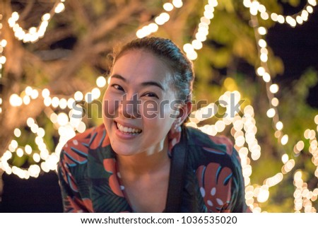 Beautiful young Asian girl smile with a bokeh light at night. #1036535020