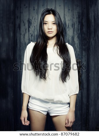 Beautiful young Asian model with long dark straight hair wearing white sheer top