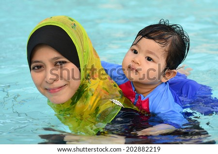 Beautiful young Asian muslim mother enjoying teaching her cute baby girl a first swimming lesson in a swimming pool