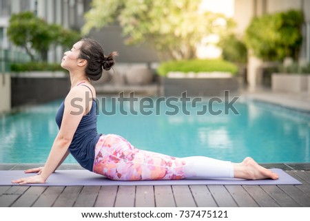 Beautiful young Asian woman doing yoga exercise with Bhujangasana posing (Cobra Pose) near swimming pool. Healthy lifestyle and good wellness concepts #737475121