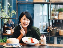 Beautiful young Asian woman eating homemade pancakes in coffee shop,food blogger.
