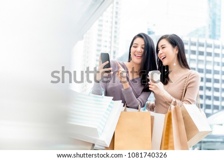 Beautiful young Asian woman friends searching for infomation online via smartphone while shopping in the city