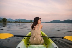 Beautiful young asian woman holding paddle in canoe on lake at evening on vacation. Leisure activity, Recreational pursuit