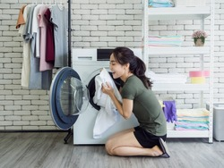 Beautiful young Asian woman housewife sitting with smiling and smelling white clean towel after washing from washing machine in laundry room.