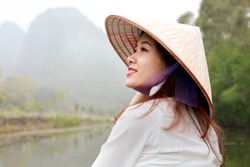 Beautiful young Asian woman in the traditional cone hat with river and misty mountains on the background