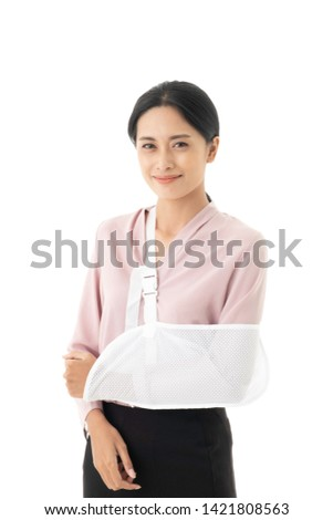 Beautiful young Asian woman is injured with a broken arm and put on arm sling.
