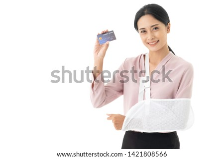 Beautiful young Asian woman is injured with a broken arm and put on arm sling. Which shows a credit card, Accident insurance business concept.