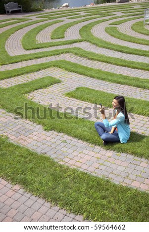 Beautiful young Asian woman laughs at a text message on her cellphone while sitting in a grass labyrinth.