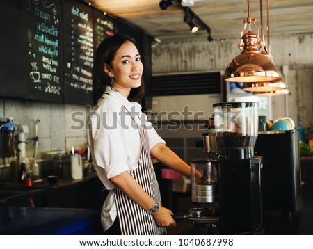 Beautiful young Asian woman making a coffee cup in cafe.