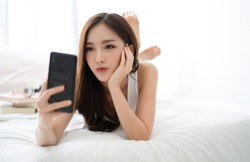 Beautiful young Asian woman making selfie using a smartphone and smiling while lying on bed. People addiction to new technology trends.