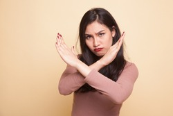 Beautiful young Asian woman say no on beige background